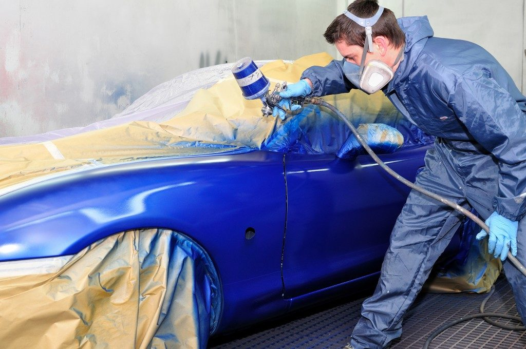 Worker painting a car in paint booth