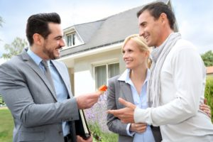 Real estate agent giving home keys to property owners