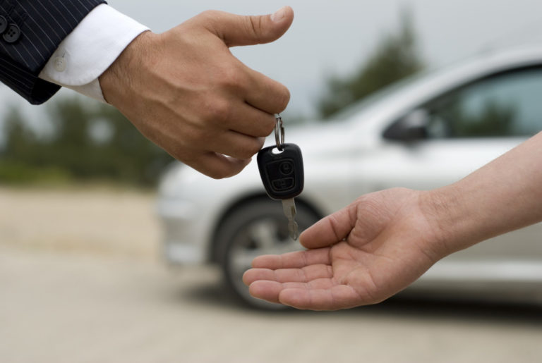 person handing over car keys