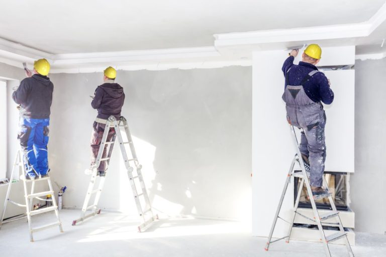 three men painting a room
