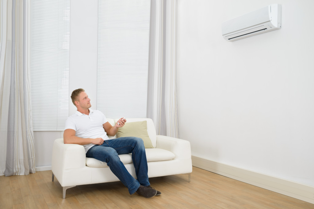 man turning on the air-conditioner